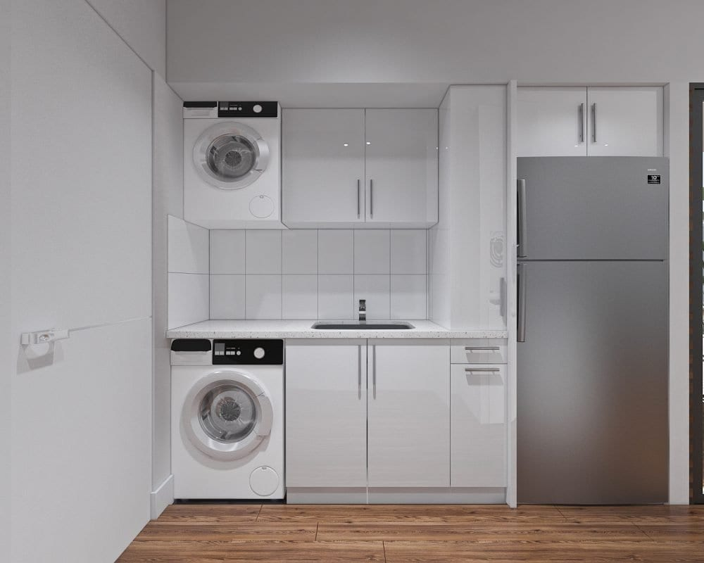 White cabinets, washing machine, faucet, and a gray refrigerator