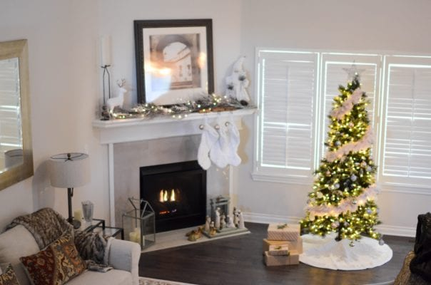 living room with gifts under christmas tree, fireplace, white wall of the house, white socks